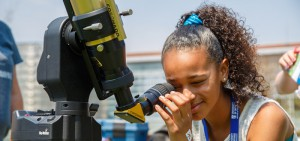 A budding scientist looks through a telescope at DC and UOIT's science rendezvous
