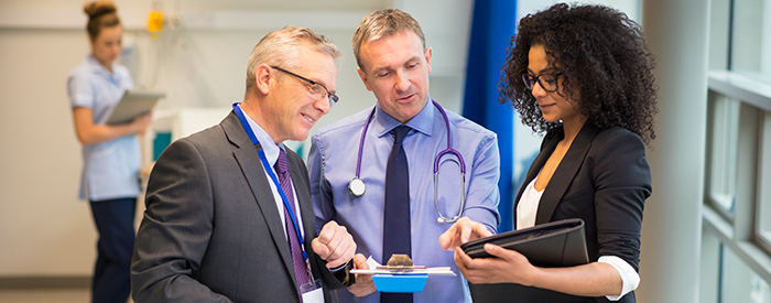 Health Care Technology Managers focus their attention on a tablet.