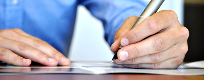 Man writing with a pen on a desk