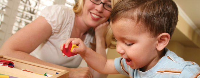 A toddler playing with blocks while a smiling woman watches him
