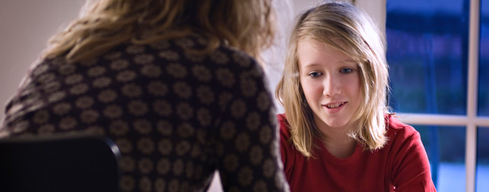 A young girl who looks worried, speaking with a reassuring adult