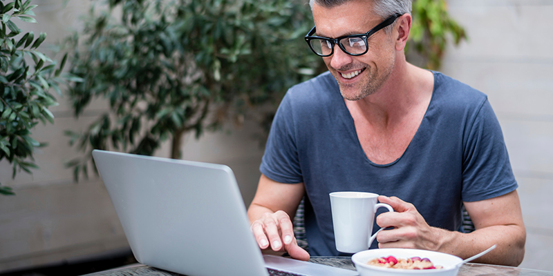 Man on laptop with lunch