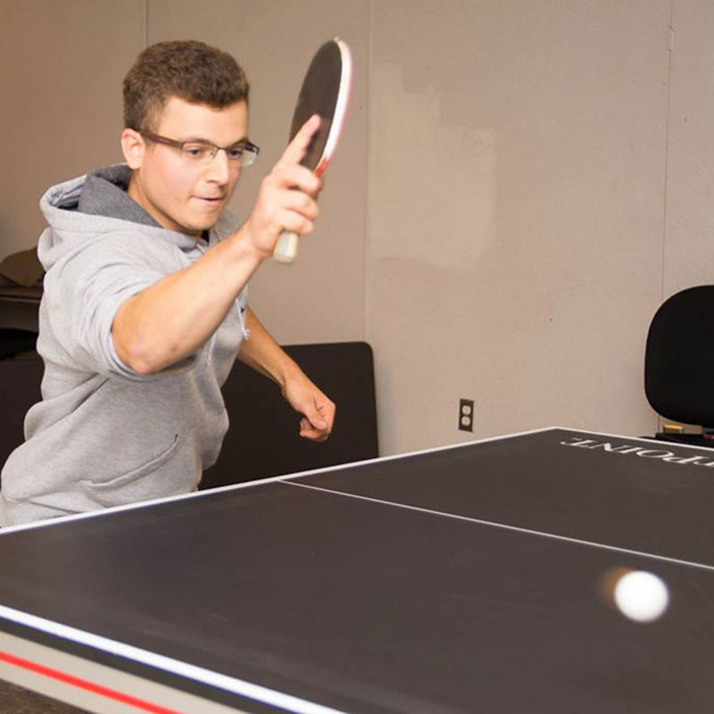 A student playing ping-pong.
