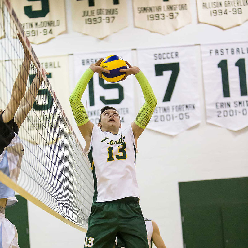 A Durham Lord Volleyball player setting the ball.