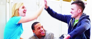 two students performing a high five while a colleague watches