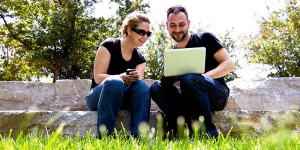 Two people sitting on rocks looking at laptop