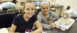 Two girls pose while sewing